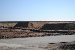 手前は舗装工事された農道。土の山はこれから整地される土。その奥が海岸林予定地