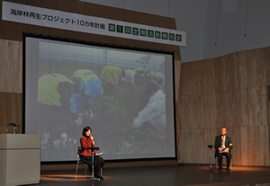 支援企業さんの担当者とトークセッションに登場した吉田さん。スクリーンの映像は企業さんのボランティアが雨の中草取りに参加した時のもの