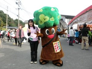 KANNEの再生・保全活動の推進キャラクター「虹松まもるくん」と事務局長の藤田さん