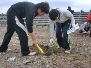 植付方法の紙を持ちながら植栽する名取北高生