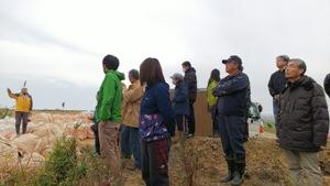 広浦の愛林碑を前に真剣に話を聞く参加者