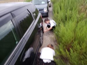 車の下に逃げたカニを必死に探す2人